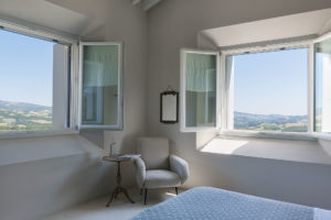 Bedroom with armchair and two windows of Malatetsa Maison de Charme in the marche hills Photographer Maria Teresa Furnari