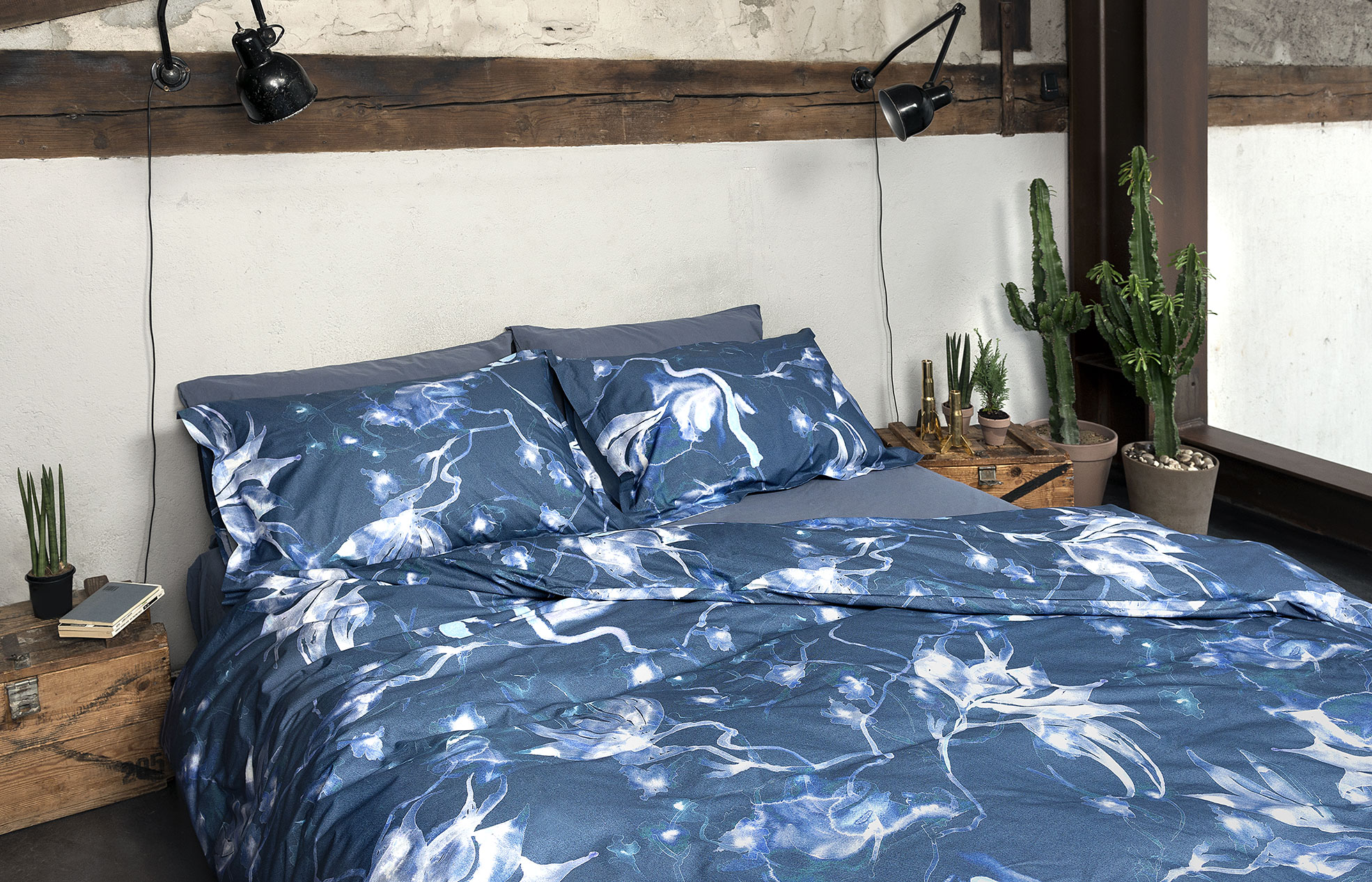 Bedroom with blue and white sheets and grey blanket of Diesel Home Linen Collection Photographer Maria Teresa Furnari