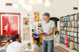 Paolo showing a book with his works in the living room of Cinema Flora Photographer Maria Teresa Furnari