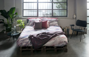 Bedroom with pink sheets and a violet blanket of Diesel Home Linen Collection Photographer Maria Teresa Furnari