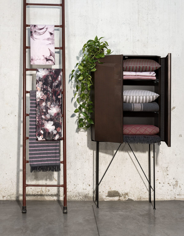 A cupboard with some pillows inside and a stair with pink towels of Diesel Home Linen Collection Photographer Maria Teresa Furnari