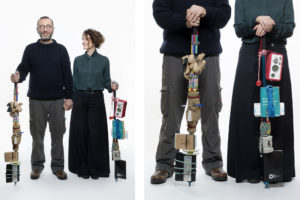 Photo of a couple with objects on their arms, the picture is part of Wearable Homes a design project by Denise Bonapace