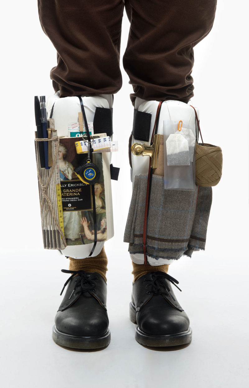 Detail of legs with objects tied on them the pictures is parte of Wearable Homes a project by Denise Paca