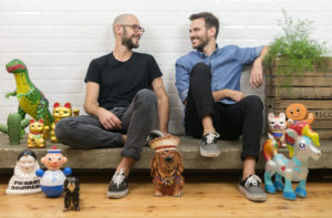 Portrait of the food influencers Gnambox surrounded by a lot of toys and funny ceramics