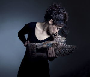 Portrait of the artist Tiziana Cera Rosco kissing a dragon statue Photographer Maria Teresa Furnari