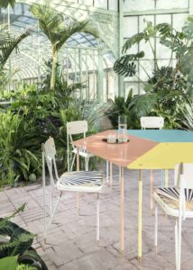 Detail of table and chairs of Aquiloni collection of the designer Derek Castiglioni shot in a greenhouse for AD USA Photographer Maria Teresa Furnari