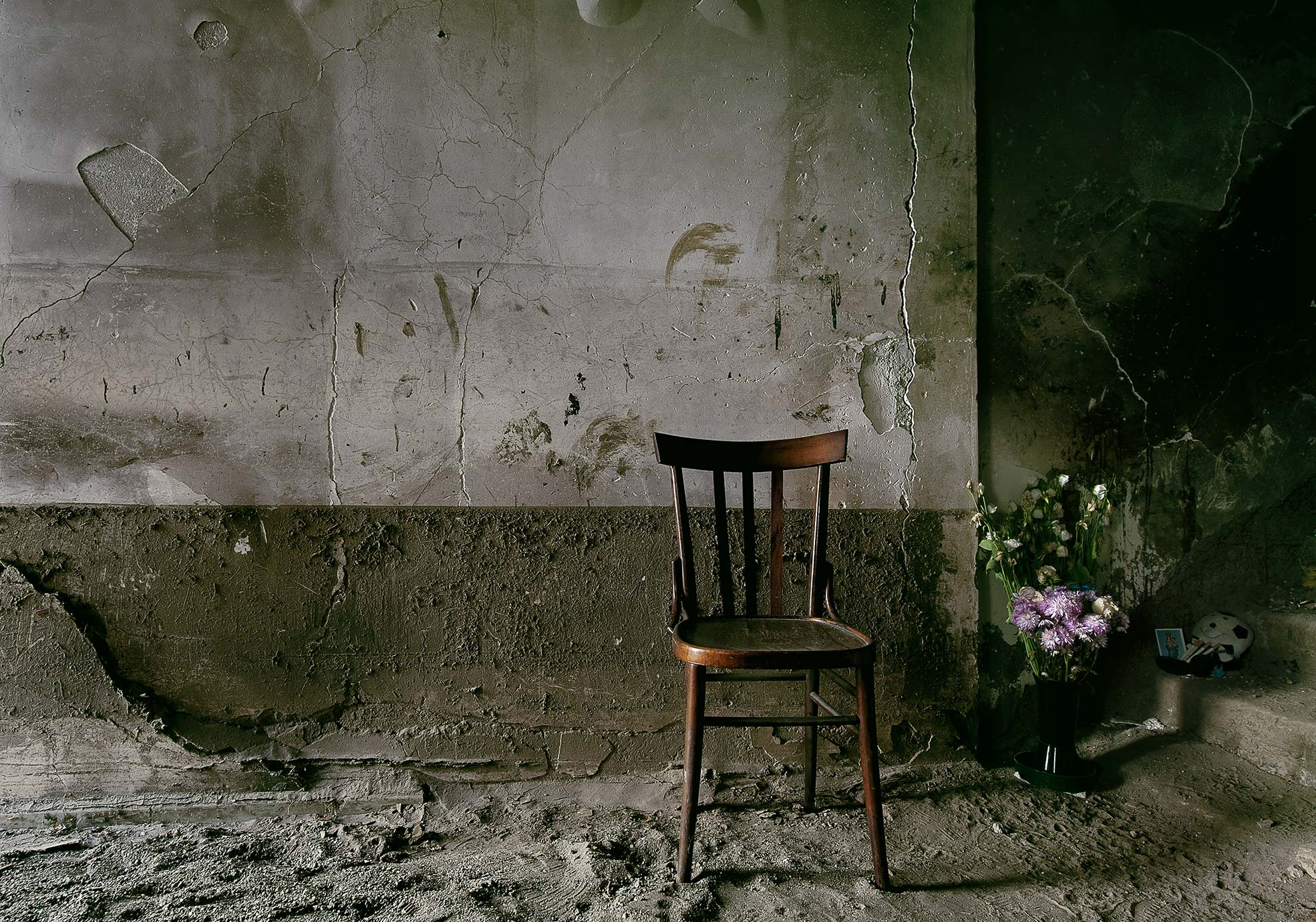 A chair without a leg and some flowers one of the trail of Giampilieri after the flood Photographer Maria Teresa Furnari