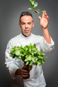 Portrait of a chef launching basil Phot