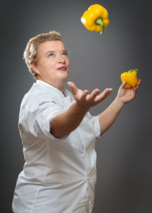 Portrait of a chef with yellow peppers flying Phot