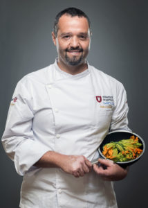 Portrait of a chef with zucchini in his cooking pan Photographer Maria Teresa Furnari